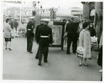 Show Str. U.S. Marines looking over show poster; girl watching Marines
