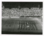 Canadian military tatoo [i.e. tattoo] in stadium; Massed bands of 2 military units