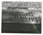 Canadian military tatoo [i.e. tattoo] in stadium; Scottish units in drill with sword dancers